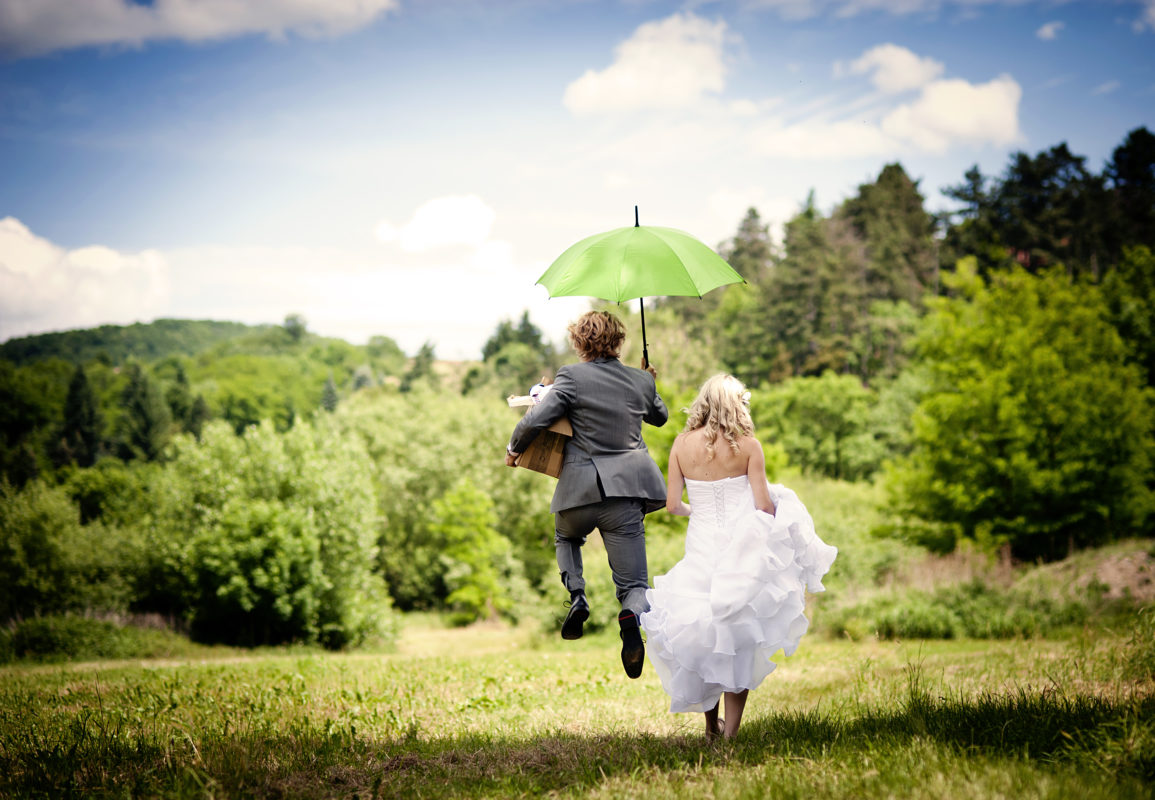 bride and groom running through field with umbrella